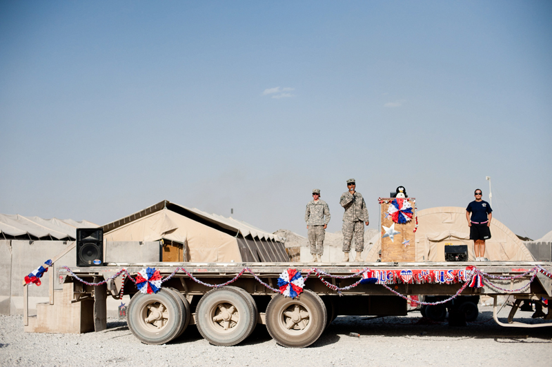 A soldier sings the US national anthem during a Fourth of July celebration at Kandahar Airfield. No holiday, no matter how small, can pass unremarked by soldiers at the large airfields. Home to the command staff and many support troops, these megabases offer broad choices of food and entertainment, while soldiers at far-flung combat outposts live in an atmosphere of austerity and relentless violence.